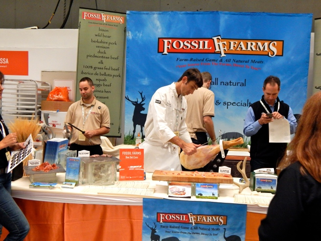 A chef cuts a smoked pig leg at the Fossil Farms